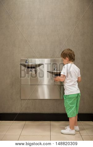 Curious kid boy drinking water from drinking fountain. Stainless Steel drinking fountains mounted at different heights. Young customer in the shop.