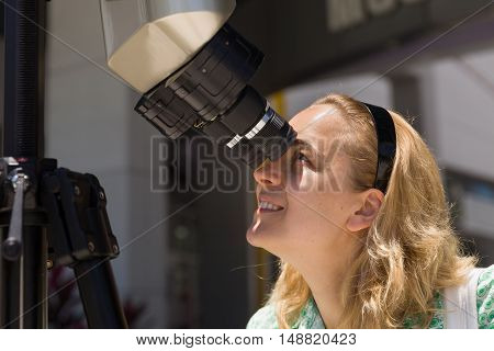 Young smiling womanlooking skyward through astronomical telescope. Beautiful girl looking through tourist telescope exploring landscape.