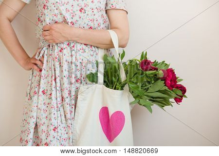 Woman holding a textile bag with beautiful bunch of red peonies. Girl's hands with bag full of peony flowers. Summer and lifestyle concept.