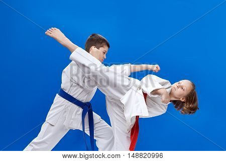 Children are beating karate blows on the blue background