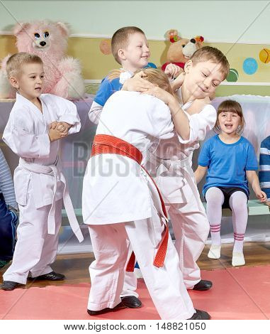 Children learn in training judo sparring on the mats