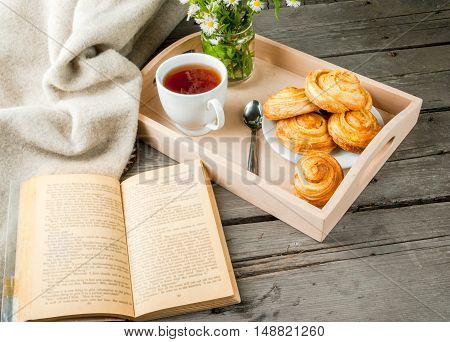 Cozy breakfast in spring or early autumn tea, freshly baked scones and bouquet of field's daisy and fascinating book. In tray. Copy space