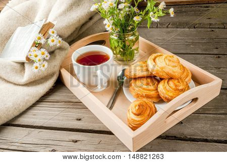 Cozy breakfast in spring or early autumn tea, freshly baked scones and bouquet of field's daisy and fascinating book. In wooden tray. Copy space
