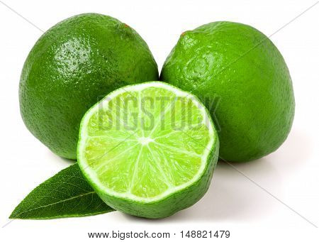 two limes with half and leaf isolated on white background.
