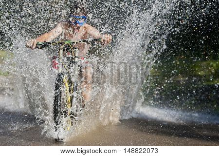 Extreme mountainbiker rides on water in river
