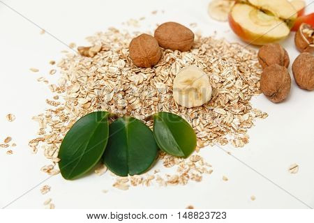 There are Banana, Apple with Walnuts and Rolled Oats,Wooden Trivet,with Green Leaves,Healthy Fresh Organic Food on the White Background,Selective Focus