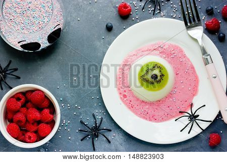 One eye panna cotta with kiwi and raspberry sauce Halloween recipe. Creative idea for kids dessert on holiday party top view