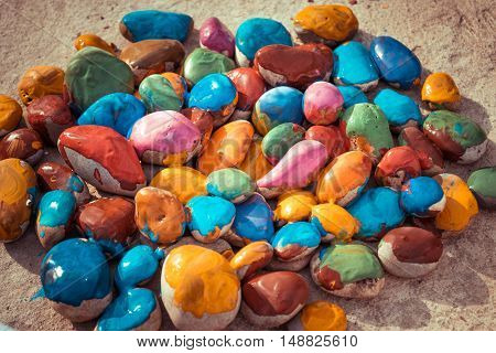 Colored stones colored paints in different colors lie on a flat surface. Close-up