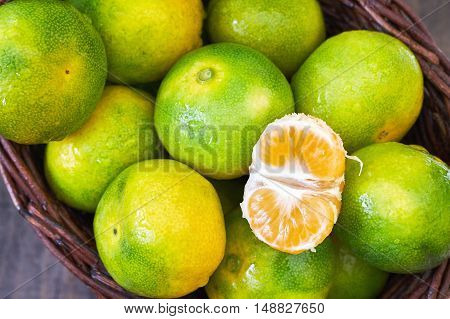 Fresh green tangerines in woven basket top view