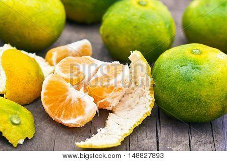 Fresh green peeled tangerine on grey rustic wooden background