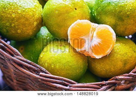 Closeup of fresh green tangerines in woven basket