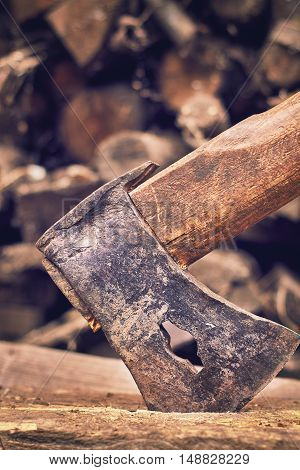 Rustic axe with pile of firewood in background. Copy space