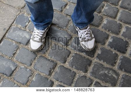 Teenage legs in sneakers and blue jeans standing on paving stones top view unusual perspective