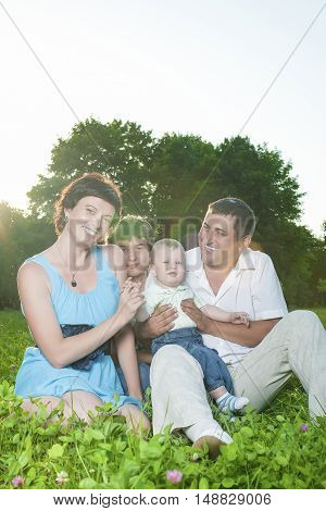 Family Concepts. Young Caucasian Family of Four People Posing Together Outdoors in Park. Sitting Embraced.Vertical Image