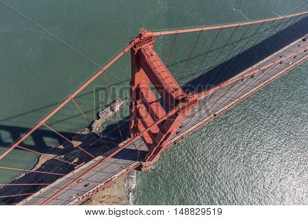 Aerial view of Golden Gate Bridge suspension tower, cable and road above San Francisco Bay in California.