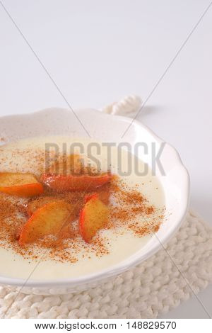 bowl of semolina pudding with apples and cinnamon on white table mat