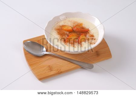 bowl of semolina pudding with apples and cinnamon on wooden cutting board