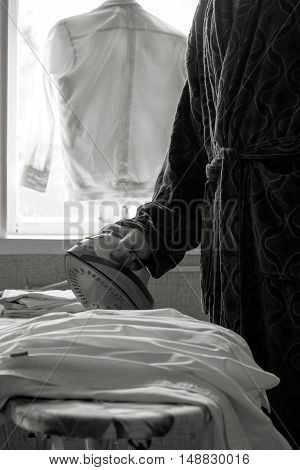 a man in robe ironing children's shirts in the early morning at the window. black and white photo