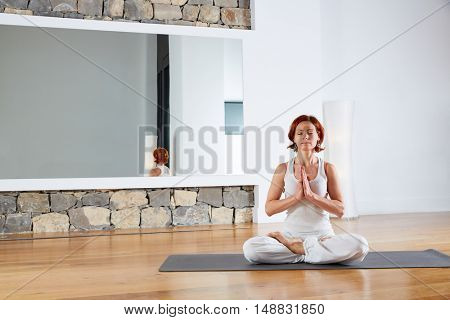 Yoga Lotus pose meditation in wooden floor gym and mirror indoor