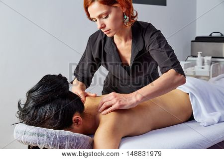 massage in woman back with physiotherapist indoor