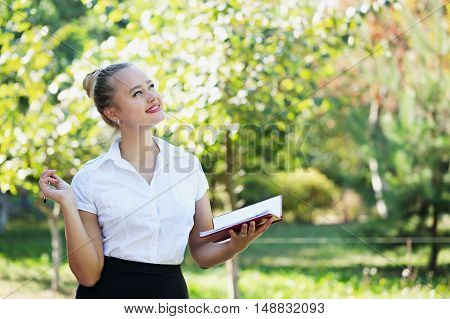 beautiful young girl with notebook on the nature