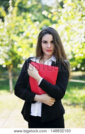 beautiful young girl with folder on the nature