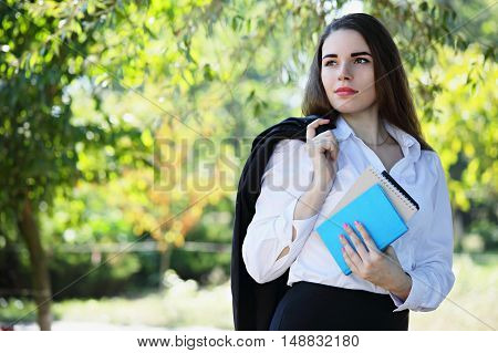 beautiful young girl with books on the nature
