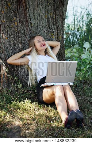 young beautiful woman with laptop on the nature of the rest