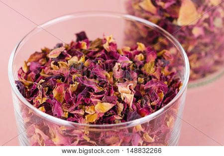 Rose petals in a glass bowl on rosy background. Dried blossoms, used for perfumes, cosmetics, teas and baths. Purple and orange colored organic herb. Isolated macro photo close up from above.