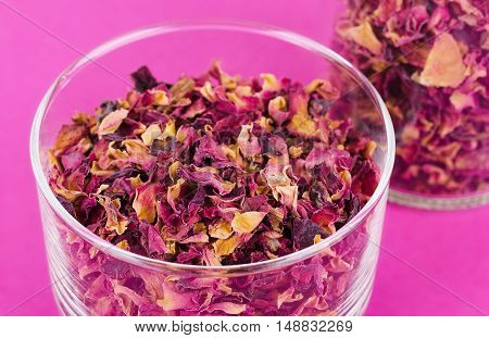 Rose petals in a glass bowl on pink background. Dried blossoms, used for perfumes, cosmetics, teas and baths. Purple and orange colored organic herb. Isolated macro photo close up from above.
