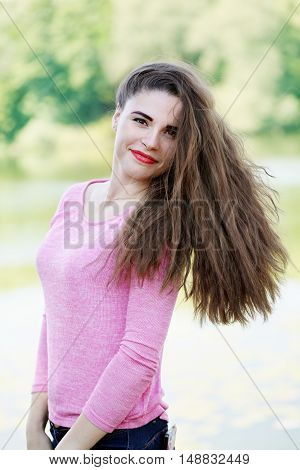 portrait of cheerful long-haired energetic woman in nature