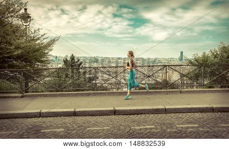 Running woman. Runner jogging at sunny day. Female listening music and fitness model training outside in Paris City with skyline and downtown view in background.