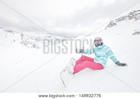 Female snowboarder wearing colorful helmet, blue jacket, grey gloves and pink pants sitting with snowboard on snow and showing thumb up hand gesture - enjoying snowboarding concept