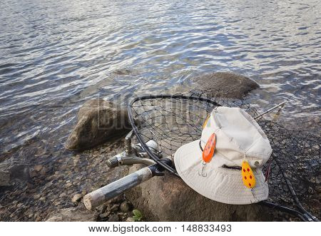 horizontal image of fishing gear consisting of a hat with fishing hooks attached and a net and fishing rod lying on a rock next to the lake.