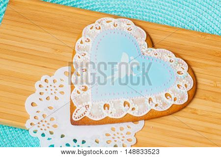 Beautiful pastel blue gingerbread with the image of a cute little girl elf and tracery doily, background of wooden planks
