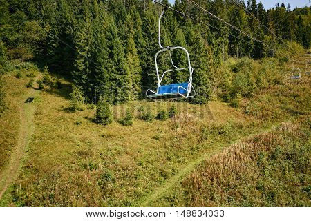 Lift seats in the Carpathians among spruce trees with walkway. Summer time