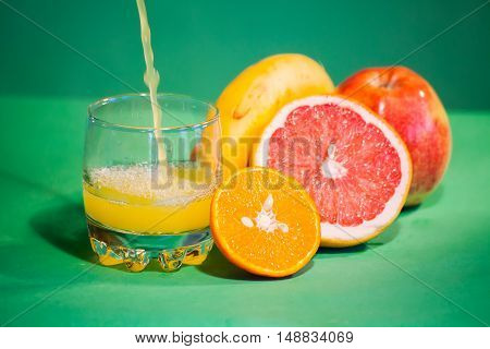 the juice is poured into a glass. Against the background of grapefruit, mandarin, banana and apple.