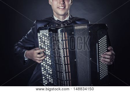 Closeup of musician playing the accordion on a black background