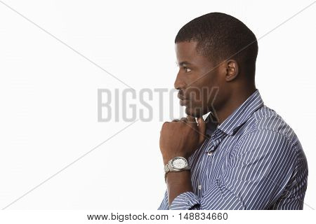 Profile of Afro-American man looking away and touching his chin while posing over white background in studio. Emotions concept.