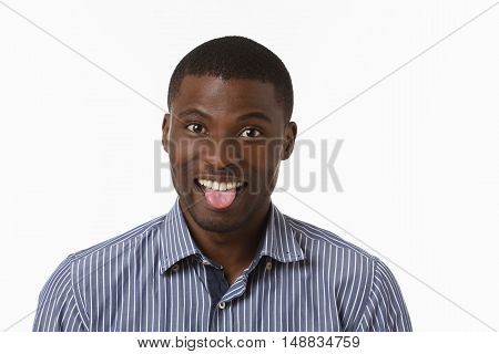 Afro-American man expressing funny emotions while posing over white background in studio. Handsome man showing his tongue to camera.