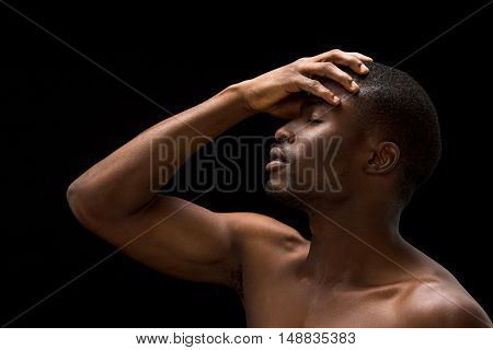 Portrait of naked passionate Afro-American man touching his head while posing over black background in studio.