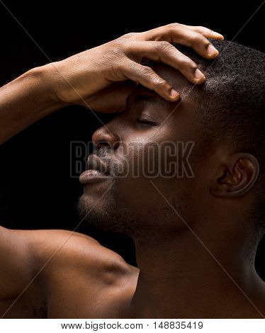 Closeup portrait of hanfsome naked passionate Afro-American man posing with his eyes closed over black background.