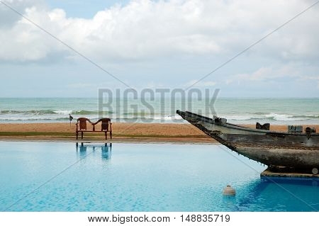 The swimming pool and old traditional boat as decoration in luxury hotel Bentota Sri Lanka