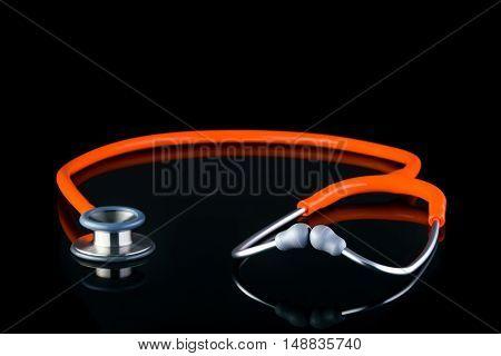 Classic stethoscope laying flat isolated on black background