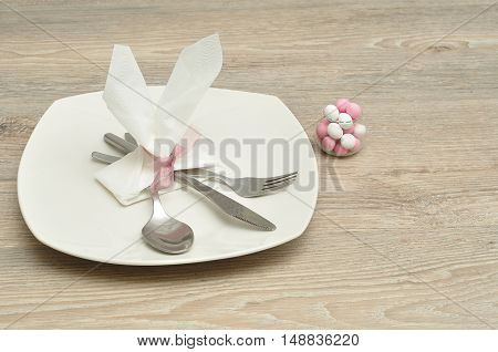 An Easter place setting with the napkin in the shape of bunny ears displayed with a plate knife fork spoon and a bowl of candy