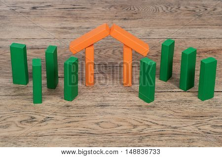 Orange house and green trees made of toy wooden blocks put on the old board