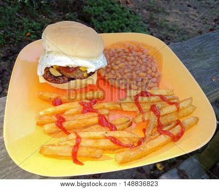 A plate with a hamburger with a sunny side up egg cheese catsup mustard grilled onions and salted french fries with baked beans on a wooden railing.