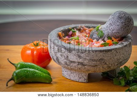 A freshly made mortar of salsa fresca, with Tomato green peppers, in a molcajete, with cilantro