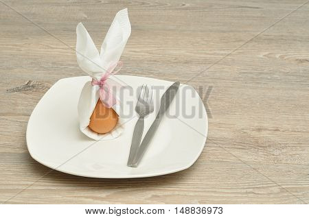 An egg in a napkin with bunny ears displayed on a plate with a knife and fork for Easter