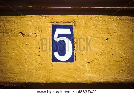 Enamelled tile door number five on yellow plaster wall